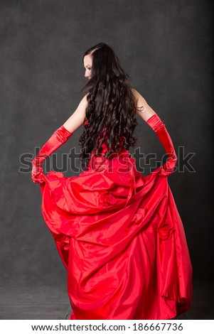 Latino Woman with long hair  in red waving dress dancing  in action with flying fabric on dark grey background - stock photo