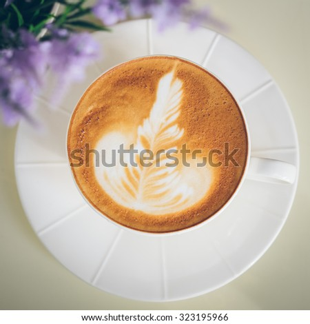 Latte art. A cup of latte coffee in a white cup, see purple flower as foreground. - stock photo