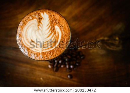 Latte art, coffee and coffee beans  on wooden background - stock photo