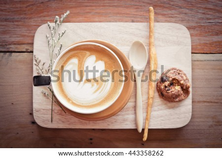 latte art coffee on the wood table and morning light in coffee shop: Coffee Vintage  style. - stock photo