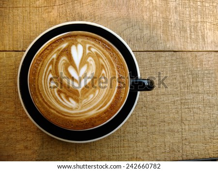 Latte art coffee on the wooden desk. - stock photo