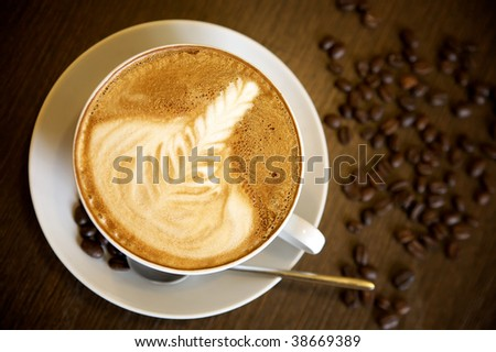 Latte art on a cappucinno and coffee-beans (selective DOF) - stock photo
