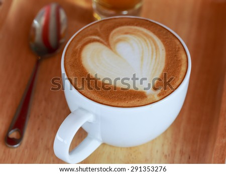 latte arts in heart shape of cappuccino hot coffee on wood tray - stock photo