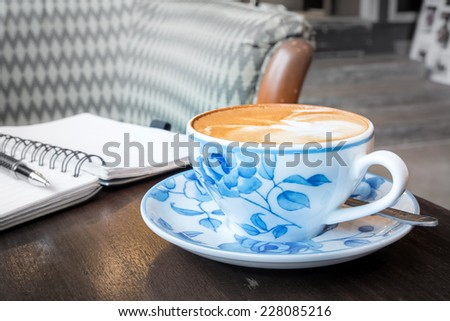Latte coffee cup with notebook and pen  - stock photo