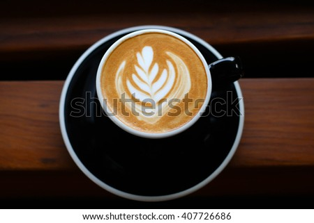 latte coffee in black cup on wooden desk - stock photo