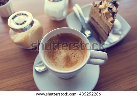 Latte coffee with coffee cake  in coffee shop in vintage tone color,view from the top. - stock photo
