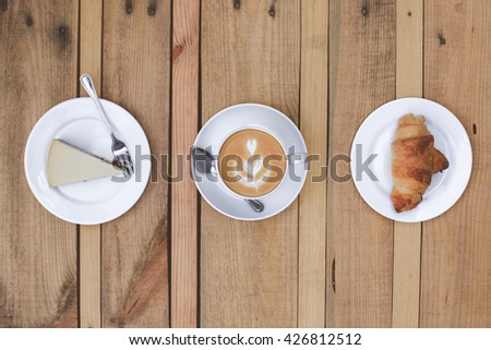 latte cup curd cake and croissant on a wooden table made of pallet - stock photo