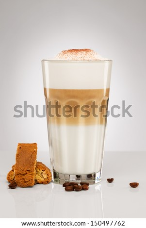 latte macchiato with chocolate powder coffee beans and cantuccini cookies on gray background - stock photo
