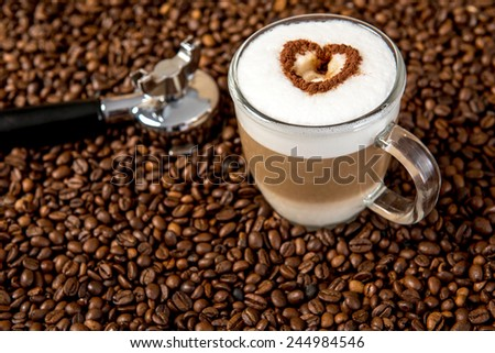 Latte Macchiato with heart on coffee beans - stock photo