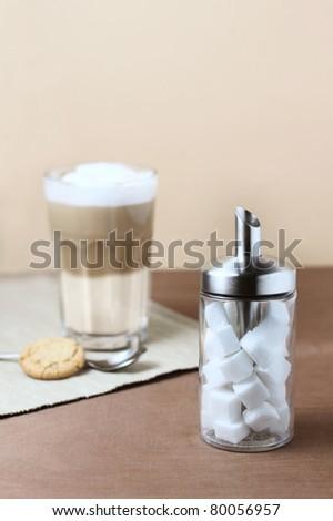 latte macciato with sugar dispenser - stock photo