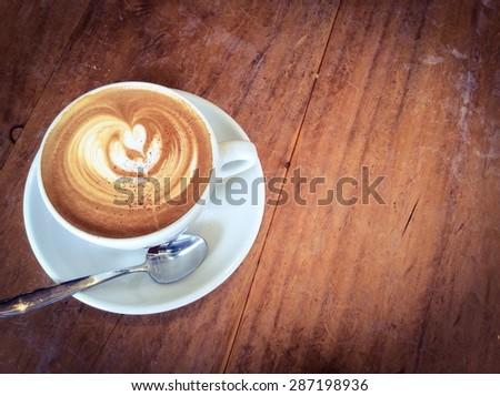 Latte or cappuccino coffee in retro filter effect  - stock photo