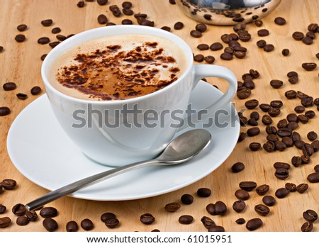 LAtte with choclate sprinkled on top in white cup with coffee beans - stock photo