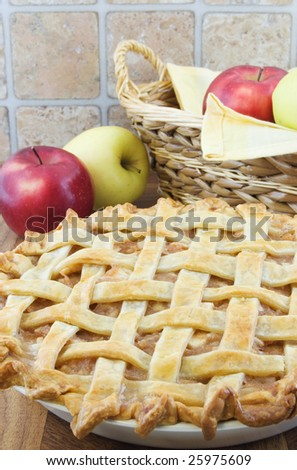 Lattice apple pie with apples and basket behind - stock photo
