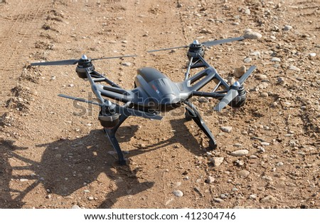 LATVIA-APRIL 25, 2016: Drones used in various commercial applications, such as journalism, filmmaking, surveying, transport, and agriculture. Drone on a gravel road before or after the flight, Latvia.