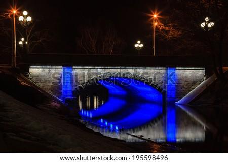Latvia Canal Bridge.  One of the pedestrian bridges spanning the city canal in Riga, capital of Latvia, is illuminated at night. - stock photo