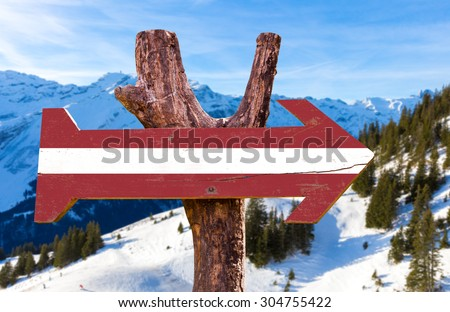 Latvia Flag wooden sign with winter background - stock photo