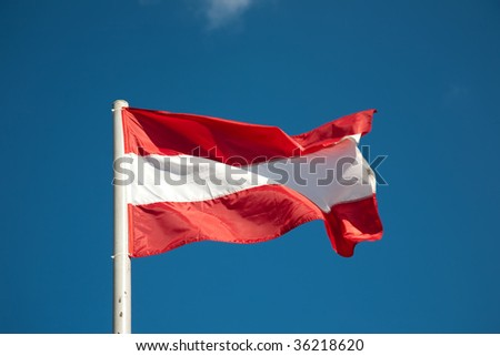 Latvian flag against blue sky - stock photo