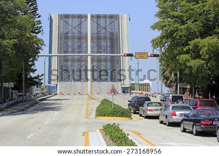 LAUDERDALE-BY-THE-SEA, FL, USA - APRIL 7, 2014: A drawbridge is raised straight up and cars wait patiently on the east side of the Intracoastal Waterway on Commercial Boulevard on a sunny day.  - stock photo
