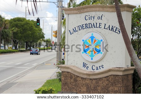 Lauderdale Lakes, FL, USA - July 11, 2014: City of Lauderdale Lakes Sign, We Care, entrance sign along the street during the day. There is an emblem on the sign of people radiating from their feet out