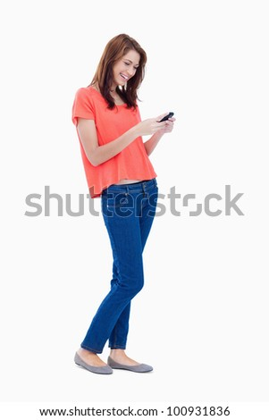 Laughing adolescent sending a text with her mobile phone - stock photo