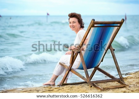 Laughing adult woman sitting in a chair on the beach and looking at you