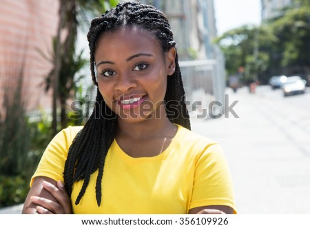 Laughing african american woman in a yellow shirt in the city