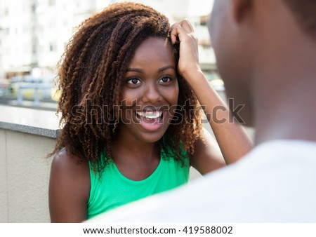 Laughing african girl flirting with friend - stock photo