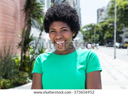 Laughing african woman in a green shirt in the city with buildings and street in the background - stock photo