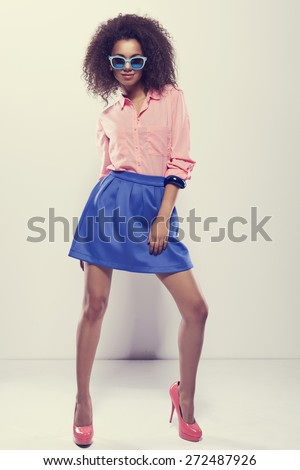Laughing African young woman with an afro hairstyle wearing sunglasses and pastel stylization - stock photo
