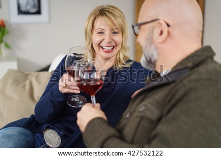 Laughing attractive middle-aged woman celebrating with her husband on a sofa at home toasting him a glass of red wine - stock photo