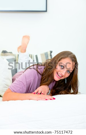 Laughing attractive woman lying on white sofa at home