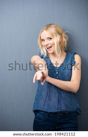 Laughing attractive young woman standing against a grey background pointing at the camera as she identifies someone or singles out her choice - stock photo