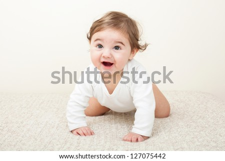 Laughing baby boy crawling on knitted blanket