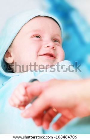 Laughing baby boy holding mamas hand