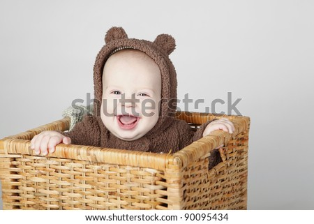 Laughing baby boy sitting in a basket wearing a fully bear suit - stock photo