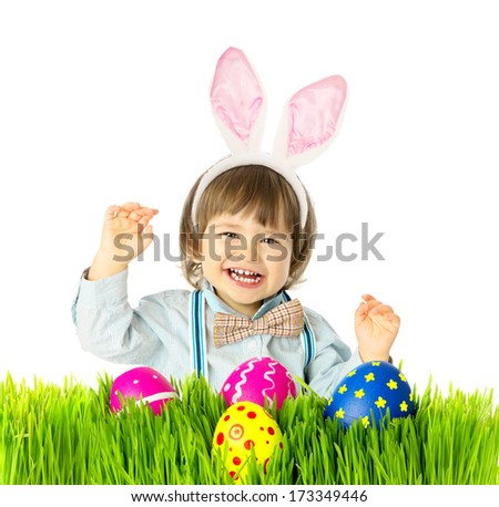Laughing baby boy with bunny ears, bow tie, suspenders hunting for Easter eggs in a green grass. Retro fashion style. Studio shot, isolated, on a white background with copy space.  - stock photo