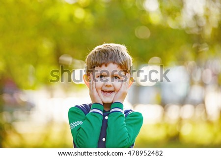 Laughing Baby holding his head in his hands with a surprised look and opened his mouth showing white teeth. Portrait outdoor.