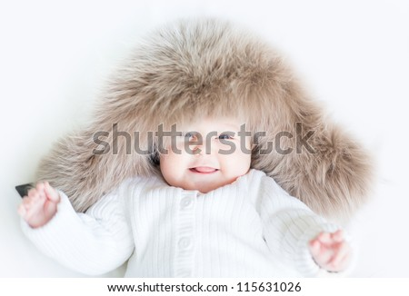 Laughing baby in a big fur hat - stock photo