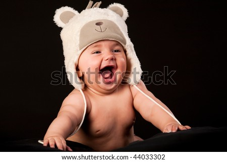 laughing baby in bear cap in black background - stock photo