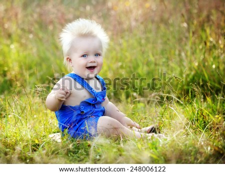 Laughing baby sitting in the grass - stock photo