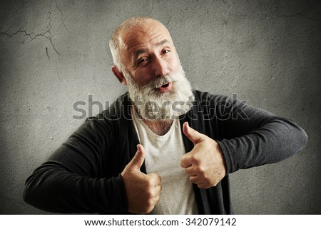 laughing bearded man showing thumbs up and looking at camera over grey wall - stock photo