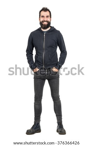 Laughing bearded punker in black hoodie with hands in pockets looking at camera. Full body length portrait isolated over white studio background.  - stock photo