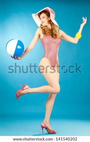 Laughing beautiful girl pin-up in a pink bikini with beach ball - stock photo