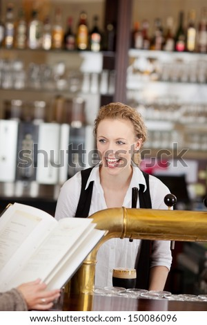 Laughing beautiful vivacious young barmaid serving drinks behind a bar counter in a pub or restaurant - stock photo