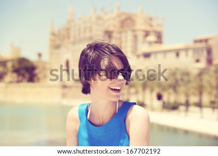Laughing beautiful young woman in sunglasses holidaying in Mallorca on a hot sunny summer day