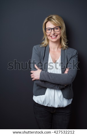 Laughing blond mature business woman wearing eyeglasses and gray sweater with folded arms leaning against blank dark wall with copy space - stock photo