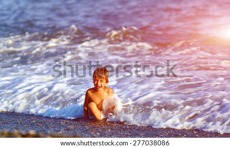 laughing boy  looks into the camera on a beach at sunset - stock photo