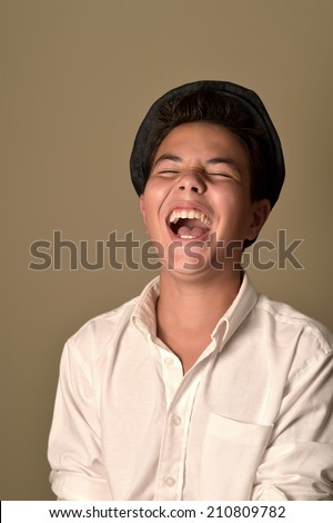 Laughing boy with a cap on a brown background  - stock photo