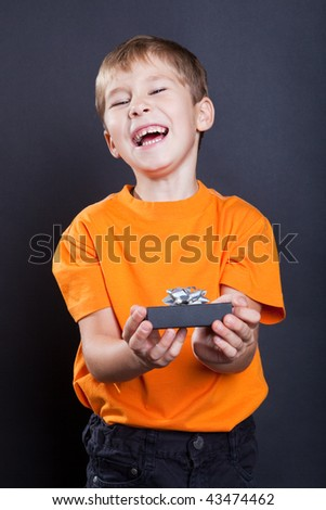 Laughing boy with a gift in hands - stock photo