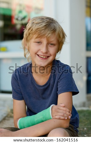 laughing boy with cast on right hand - stock photo